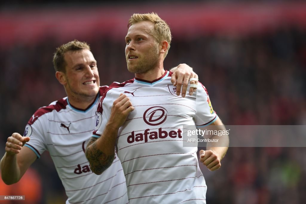 Burnley's Scottish-born Canadian midfielder Scott Arfield (R) celebrates with Burnley's New Zealand striker Chris Wood after scoring the opening goal of the English Premier League football match between Liverpool and Burnley at Anfield in Liverpool, north west England on September 16, 2017. / AFP PHOTO / Paul ELLIS / RESTRICTED TO EDITORIAL USE. No use with unauthorized audio, video, data, fixture lists, club/league logos or 'live' services. Online in-match use limited to 75 images, no video emulation. No use in betting, games or single club/league/player publications. /