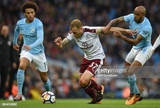 Burnley's Scottishborn Canadian midfielder Scott Arfield vies with Manchester City's German midfielder Leroy Sane and Manchester City's English...