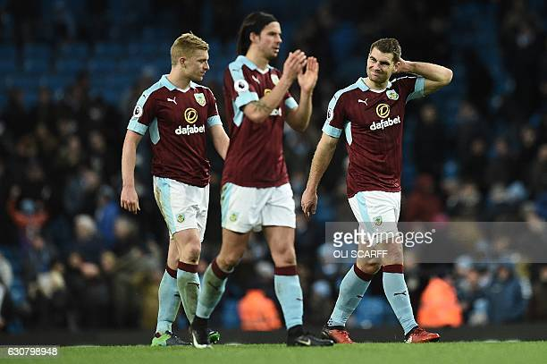 Burnley's Welsh striker Sam Vokes reacts as he leaves the pitch with Burnley's English defender Ben Mee and Burnley's Scottish midfielder George Boyd...