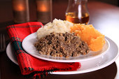 Scottish Haggis Serving For A Traditional Rabbie Burns Night Dinner With Neeps And Tatties A Glass Of Scotch Whiskey, Against A Royal Stuart Tartan Napkin