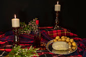 Fresh haggis and potatoes on tartan fabrics with heather and candle sticks