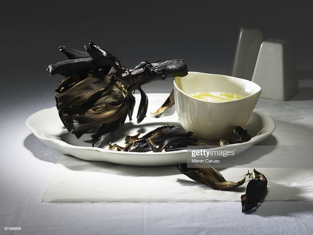 Burnt artichoke with butter on a white plate : Stock Photo