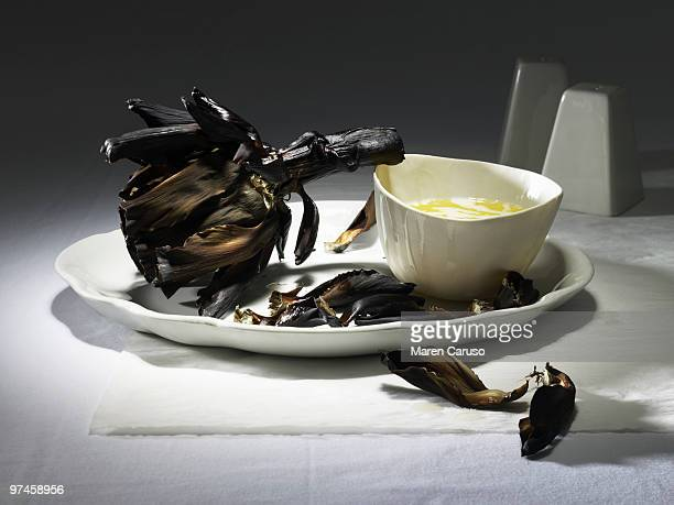 Burnt artichoke with butter on a white plate