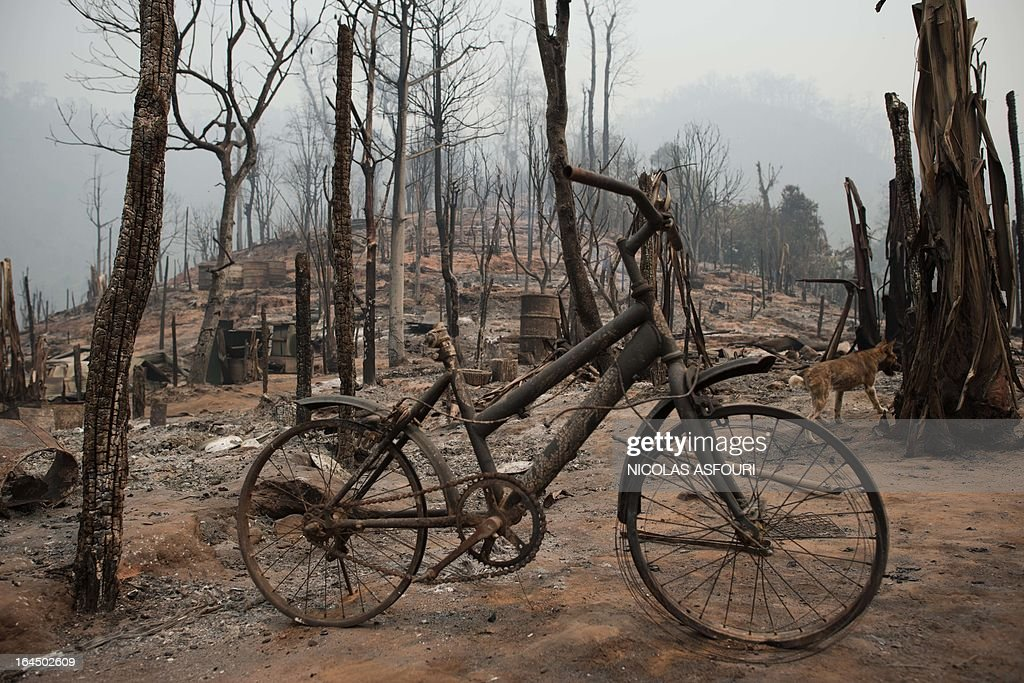 A burnt bicycle stands among debris at the Mae Surin camp in Mae Hong Son province on March 24, 2013. Thai rescue workers picked through the ashes of hundreds of shelters for Myanmar refugees, after a ferocious blaze swept through a camp in northern Thailand killing 35 people. AFP PHOTO/ Nicolas ASFOURI