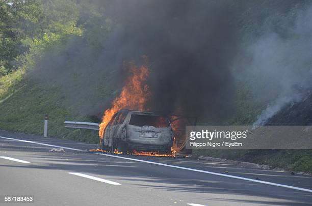 Burnt Car At Roadside By Hill