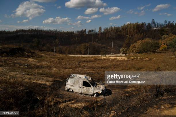 A burnt car lays on a field in the village of Travanca do Mondego on October 17 2017 in Coimbra region Portugal At least 37 people have died in fires...