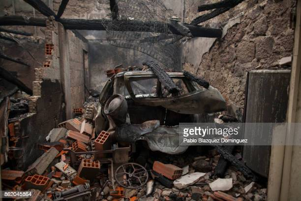 A burnt car remains inside a house in the village of Vila Nova near Vouzela on October 16 2017 in Viseu region Portugal At least 30 people have died...