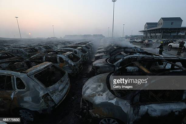 Burnt cars are seen in the debris following the explosions of a warehouse in Binhai New Area on August 13 2015 in Tianjin China At least 17 people...