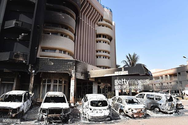 Burnt cars sit outside the Splendid Hotel and Cappuccino restaurant following a jihadist attack in Ouagadougou on January 16 2016 At least 26 people...
