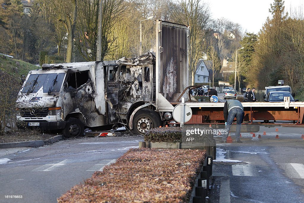 A burnt cash-in-transit (CIT) vehicle (L) is seen after an attack in Bois-Guillaume, near Rouen, northwestern France, on February 18, 2013. Two CIT security staff were slightly injured.