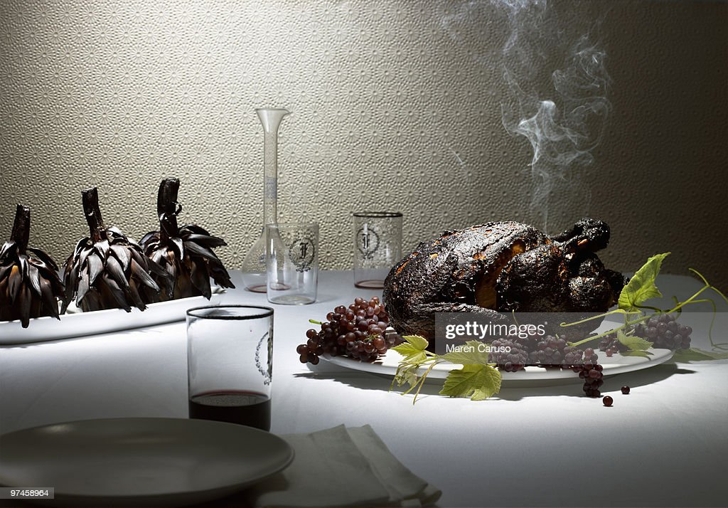 Burnt Chicken & artichokes on a nice dining table : Stock Photo