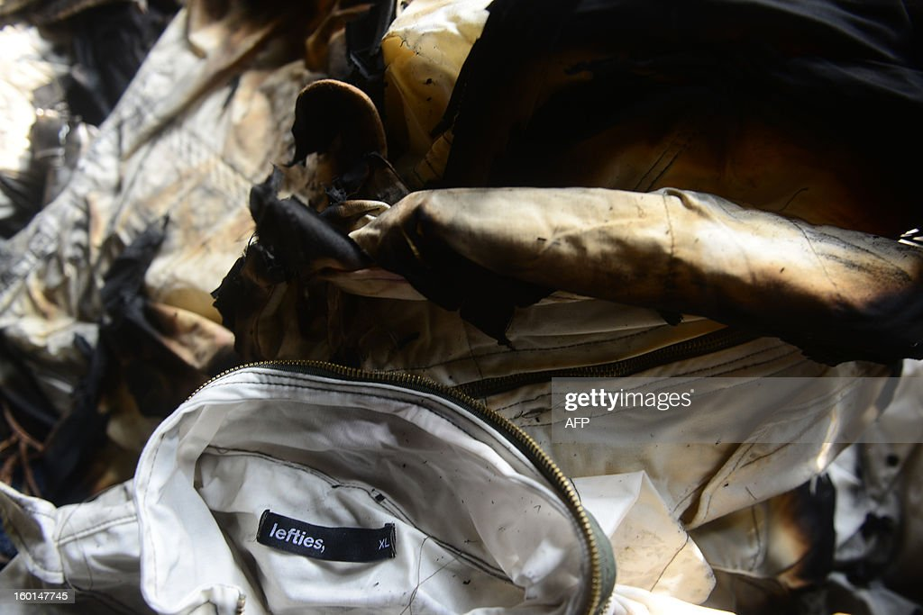 Burnt clothing form 'Lefties' lies amongst the debris after a fire swept though a garment factory in Dhaka on January 27, 2013. At least seven female workers were killed on January 26 after a blaze swept through a small garment factory in the Bangladeshi capital of Dhaka, police and fire officials said. AFP PHOTO/Munir uz ZAMAN