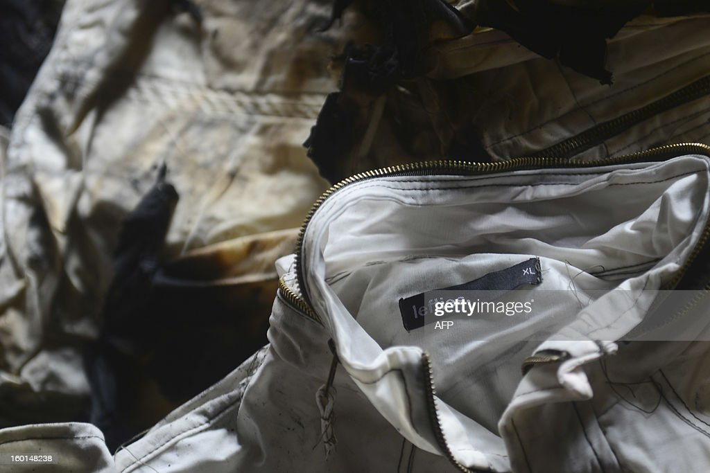 Burnt clothing with the clothing tag 'Lefties' lies amongst the debris after a fire swept though a garment factory in Dhaka on January 27, 2013. At least seven female workers were killed on January 26 after a blaze swept through a small garment factory in the Bangladeshi capital of Dhaka, police and fire officials said. AFP PHOTO/Munir uz ZAMAN