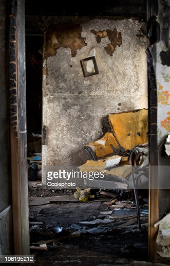 Burnt, Damaged Interior of Home with Destroyed Chair and Books