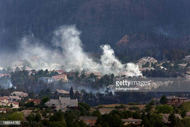 Burnt hillside with smoking homes in Colorado Springs