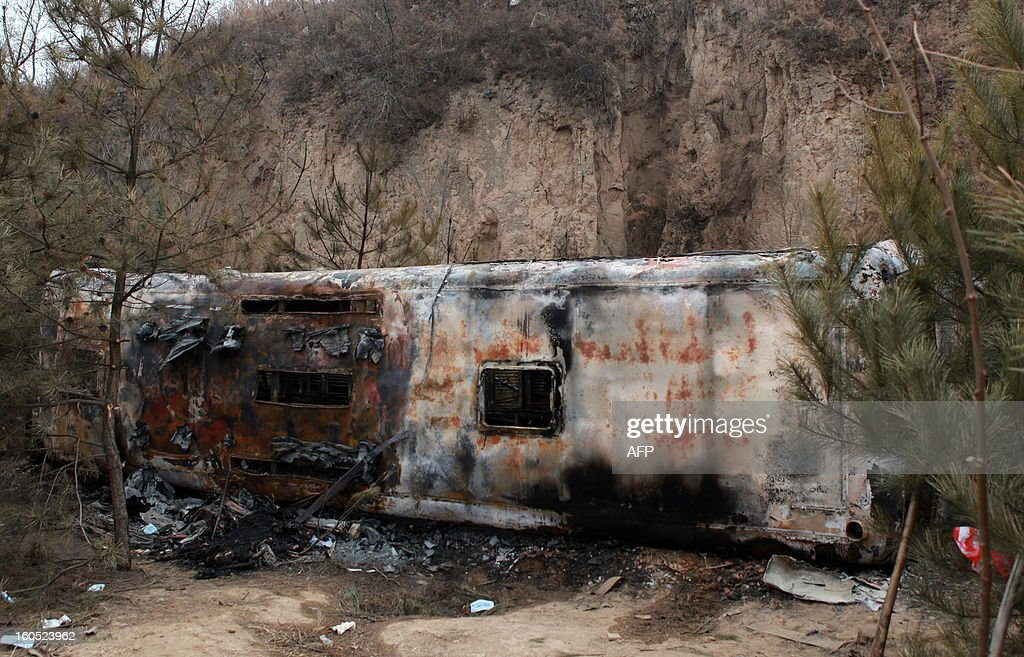 A burnt out bus lies on the ground after it plunged off a road and down a hill, catching fire after the impact, in Ningxian, northwest China's Gansu province on February 2, 2013. The accident took the lives of 18 people. CHINA OUT AFP PHOTO