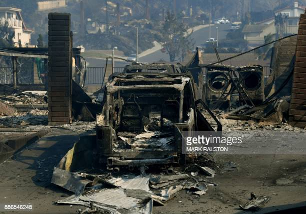 Burnt out cars and a house are seen during the Thomas wildfire in Ventura California on December 5 2017 Firefighters battled a windwhipped brush fire...