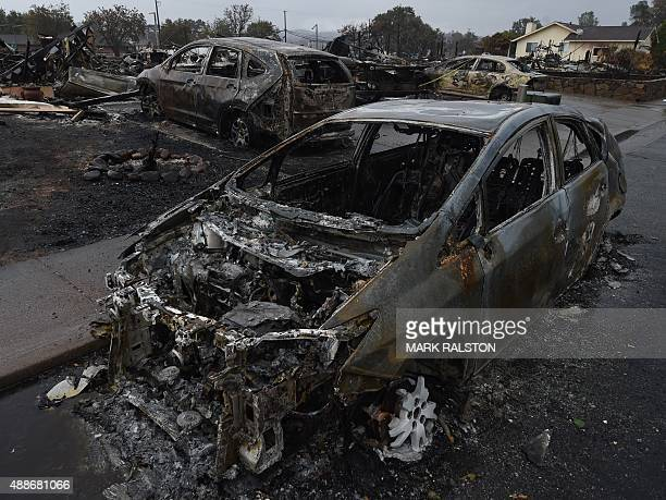 Burnt out cars lie in the street after the Valley Fire swept through the town of Middletown California on September 16 2015 The governor of...