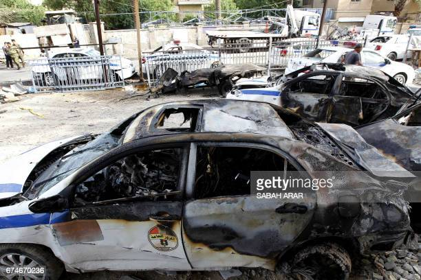 Burnt police cars are seen at the site of a blast in the Iraqi capital Baghdad on April 29 2017 A car bomb attack on the traffic police compound in...