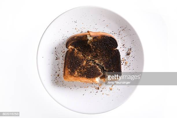 Burnt toast on white plate and white background.