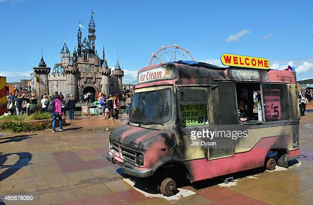 A burntout ice cream van sells Souvenir programmes in front of the fairy castle as Banksy's Dismaland Bemusement Park opens to the public on August...
