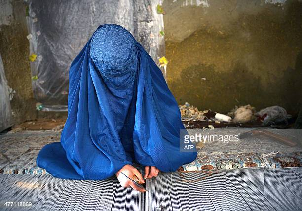 A burqaclad Afghan refugee woman makes a carpet at the Khorasan refugee camp near Peshawar on March 7 ahead of International Women's Day Some five...