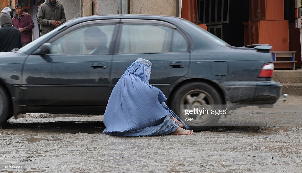 A burqa-clad Afghan resident begs on the street on a rainy day in Kabul on November 6, 2013. Despite massive injections of foreign aid since the fall of the Taliban in 2001, Afghanistan remains desperately poor as it attempts to recover from decades of conflict. AFP PHOTO / Farshad USYAN