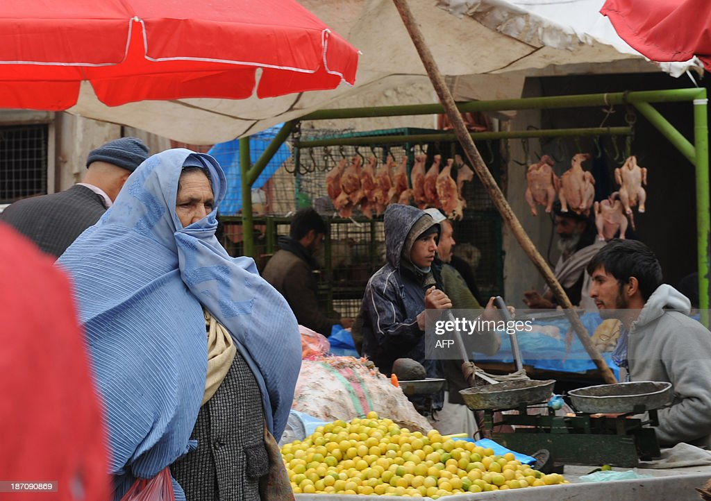 A burqa-clad Afghan resident walks through a market on a rainy day in Kabul on November 6, 2013. Despite massive injections of foreign aid since the fall of the Taliban in 2001, Afghanistan remains desperately poor as it attempts to recover from decades of conflict. AFP PHOTO / Farshad USYAN