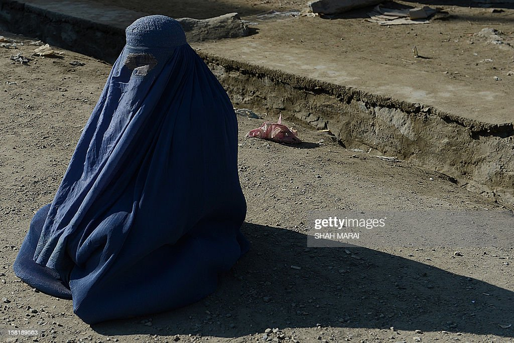 A burqa-clad Afghan woman begs for alms near a cemetery outside The Kart-e-Sakhi shrine in Kabul on December 11, 2012. Afghanistan has made some progress in using the law to protect women against violence but many still suffer horrific abuse at the hands of men, a UN report said on December 11. AFP PHOTO/ SHAH Marai