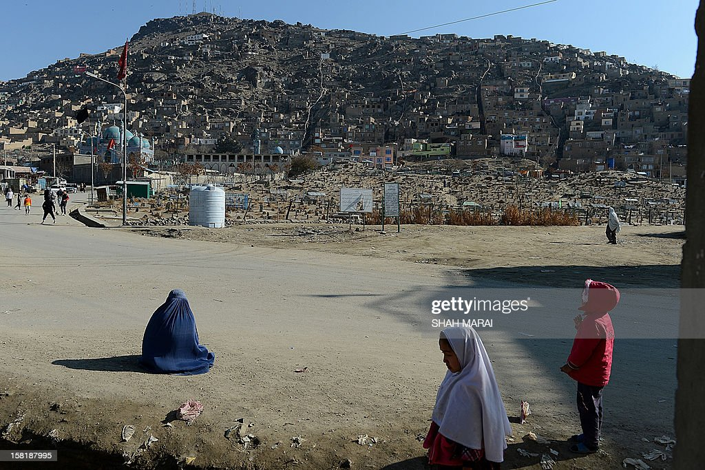A burqa-clad Afghan woman (L) begs near a cemetery outside The Kart-e-Sakhi shrine in Kabul on December 11, 2012. Afghanistan has made some progress in using the law to protect women against violence but many still suffer horrific abuse at the hands of men, a UN report said on December 11. AFP PHOTO/ SHAH Marai