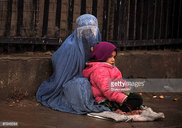 A burqaclad Afghan woman sits with her child and begs for money as it rains in Kabul on February 25 2010 Unemployment in Afghanistan is estimated to...