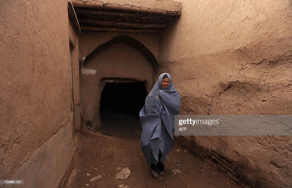 A burqaclad Afghan woman walks in the old part of Herat on November 23 2011 A landmark law aiming to protect Afghan women's rights by criminalising...