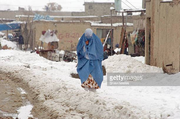A burqaclad Afghan woman walks through snow in Kabul 08 January 2008 Snow has started falling across Afghanistan as winter envelops Central Asia AFP...