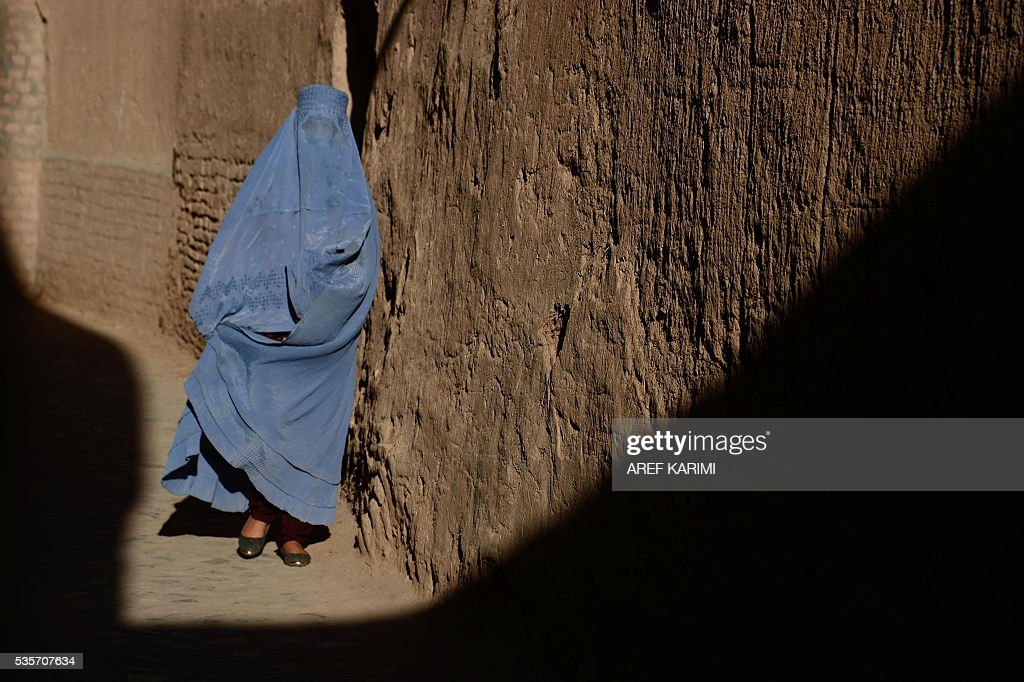 A burqa-clad Afghan woman walks through the old part of Herat on May 29, 2016. / AFP / AREF