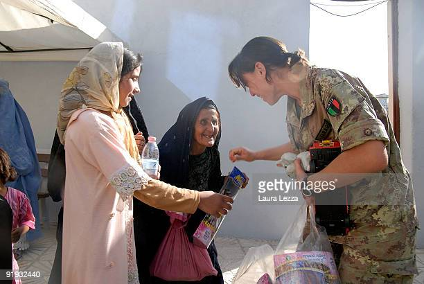 Burqaclad Afghan women and Iranian women queue with their children for medical treatment at Italian PRT on September 19 2009 in Herat Afghanistan A...