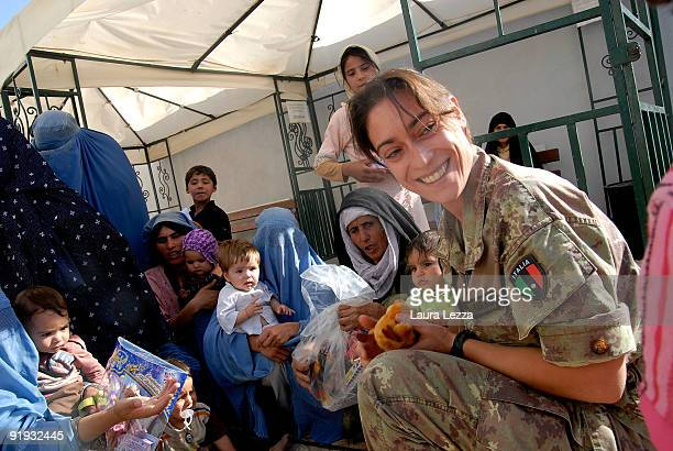 Burqaclad Afghan women queue with their children for medical treatment at Italian PRT on September 19 2009 in Herat Afghanistan A woman soldier of...