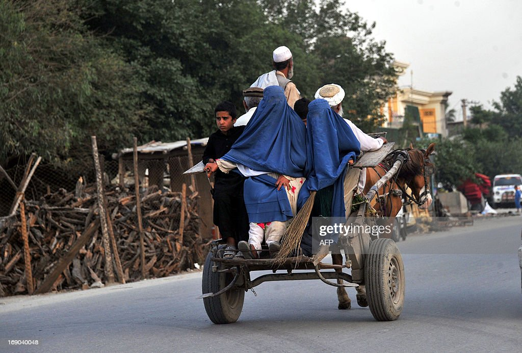 Burqa-clad Afghan women ride on the back of a horse-driven cart in Jalalabad on May 18, 2013. Some nine million Afghans or 36 percent of the population are living in 'absolute poverty' while another 37 percent live barely above the poverty line, according to a UN report. AFP PHOTO/Noorullah SHIRZADA