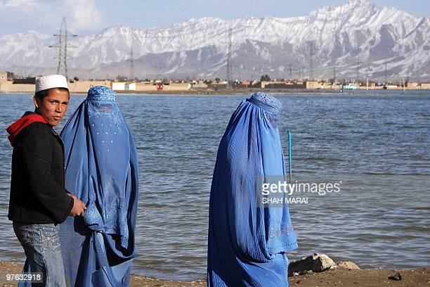 Burqaclad Afghan women walk near Shuhada lake in Kabul on February 24 2009 The small polluted lake in the centre of the Afghan capital is full due to...