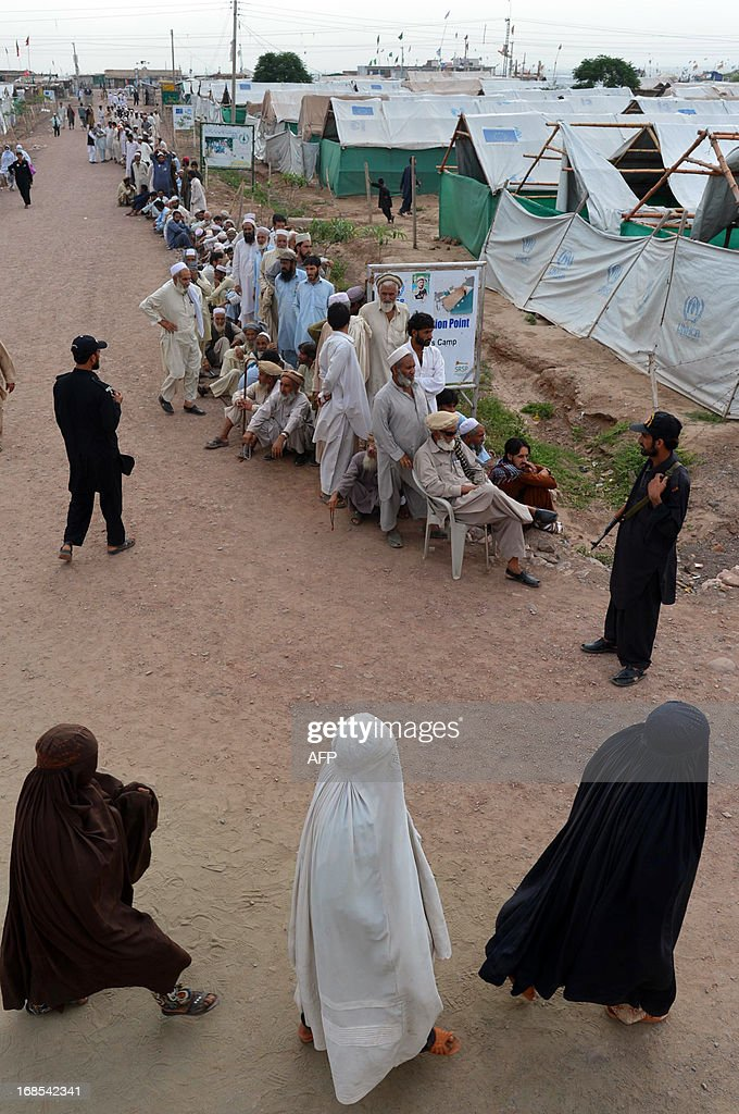 Burqa-clad internally displaced Pakistani's arrive to cast their vote as they walk past a long queue of other voters outside a polling station in Pakistan's largest refugee camp, Jalozai some 35 kms outside Peshawar on May 11, 2013. Pakistanis queued up to vote in landmark elections on May 11, defying Taliban attacks to cast their ballots in polls marking a historic democratic transition for the nuclear-armed state.