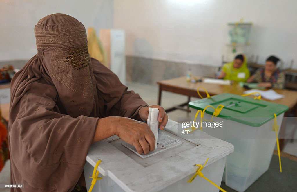 A burqa-clad Pakistani woman casts her vote at a polling station in Peshawar on May 11, 2013. Millions of Pakistanis turned out to vote in landmark elections on May 11, defying deadly Taliban attacks to take part in an historic democratic transition for the nuclear-armed state.