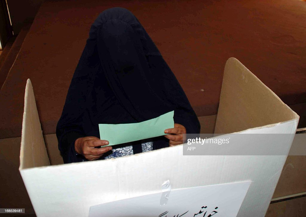 A burqa-clad Pakistani woman folds a ballot paper before casting her vote at a polling station in Chaman, the border town of Pakistan on May 11, 2013. Pakistani voters went to the polls on May 11, braving Taliban threats to cast their ballots in an election marking a historic democratic transition for the nuclear-armed state. Queues began to form before polling stations opened at 8:00 am (0300 GMT). More than 100 people including women and the elderly waited patiently to vote at one school building on the outskirts of Islamabad.