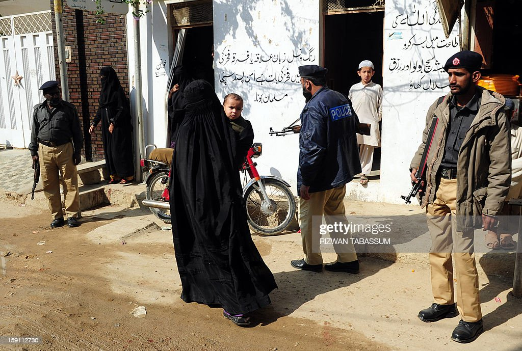 A burqa-clad Pakistani woman holds her child as she walks past police-men outside a polio vaccination center in Karachi on January 8, 2013. Pakistan is providing paramilitary and police support to polio vaccinations being resumed discreetly in the northwest after a series of attacks on medical workers, officials said. UN agencies suspended work on a nationwide campaign to inoculate children against the highly infectious disease after nine health workers were murdered in a string of attacks in the northwest and Karachi in December 2012. AFP PHOTO/Rizwan TABASSUM