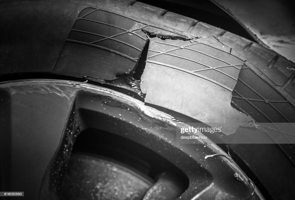 Burst car tire after accident : Stock Photo