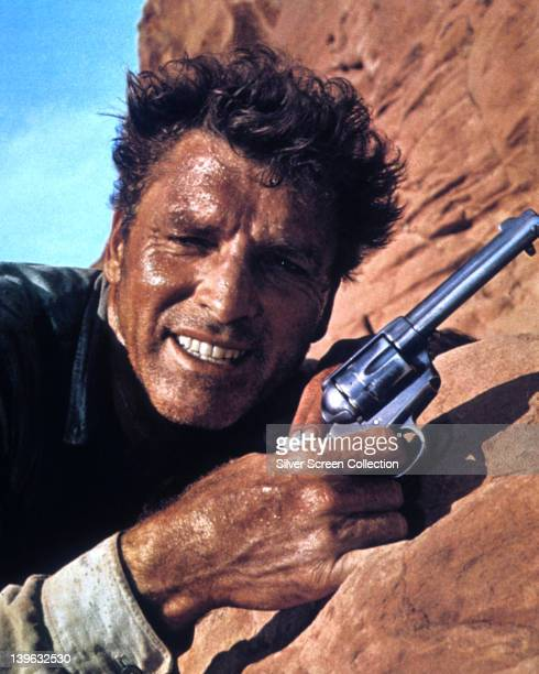 Burt Lancaster US actor sweating while standing close to a rock holding a handgun in a publicity still issued for the film 'The Professionals' USA...