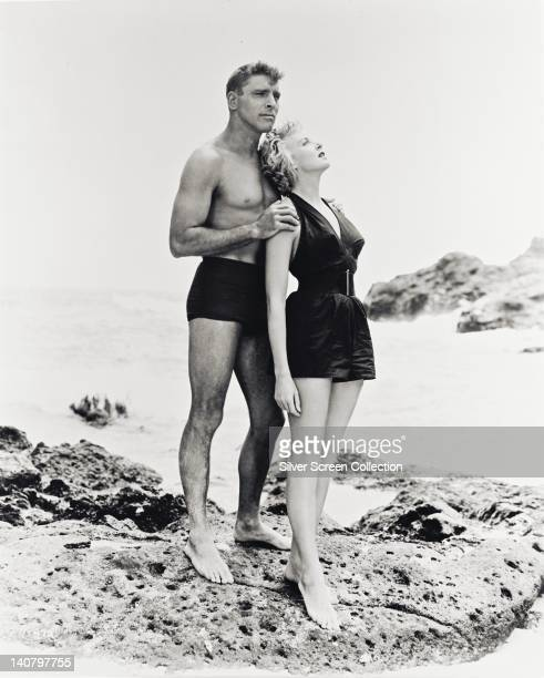 Burt Lancaster US actor wearing swimming trunks with hands on the shoulders of Deborah Kerr British actress wearing a swimsuit in a publicity...