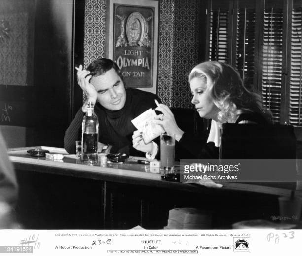 Burt Reynolds sitting at a bar having a cigarette with Catherine Deneuve in a scene from the film 'Hustle' 1975