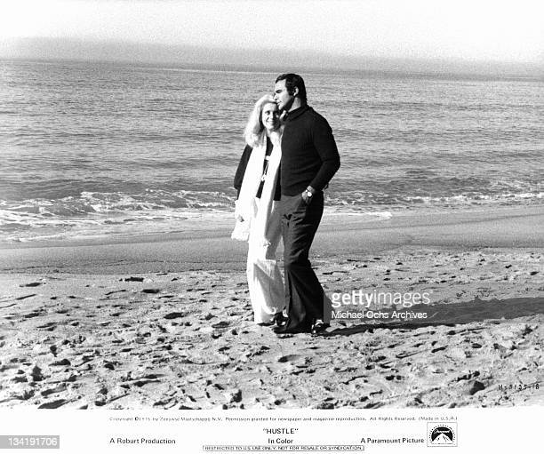 Burt Reynolds takes a romantic walk on the beach with call girl Catherine Deneuve in a scene from the film 'Hustle' 1975