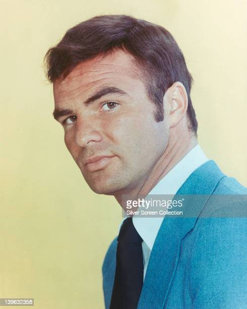 Burt Reynolds US actor wearing a blue jacket a white shirt and a black tie in a studio portrait against a yellow background issued a publicity for...