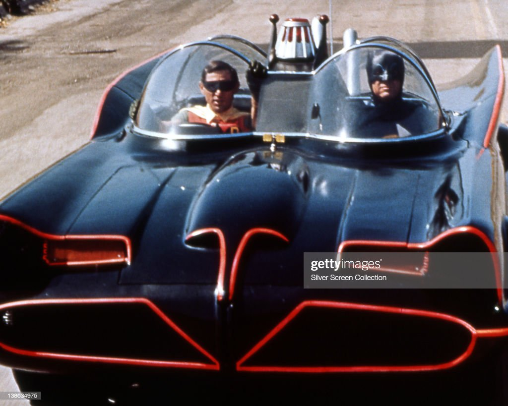 Burt Ward US actor and Adam West US actor both in costume as the 'Dynamic Duo' riding in the Batmobile in a publicity still issued for the television...