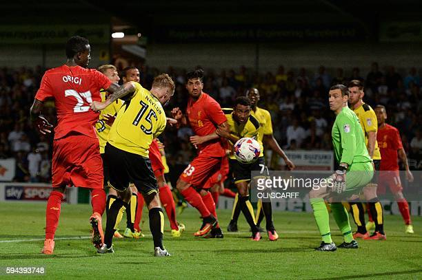 Burton Albion's English midfielder Tom Naylor scores an own goal for Liverpool's third during the English League Cup second round football match...